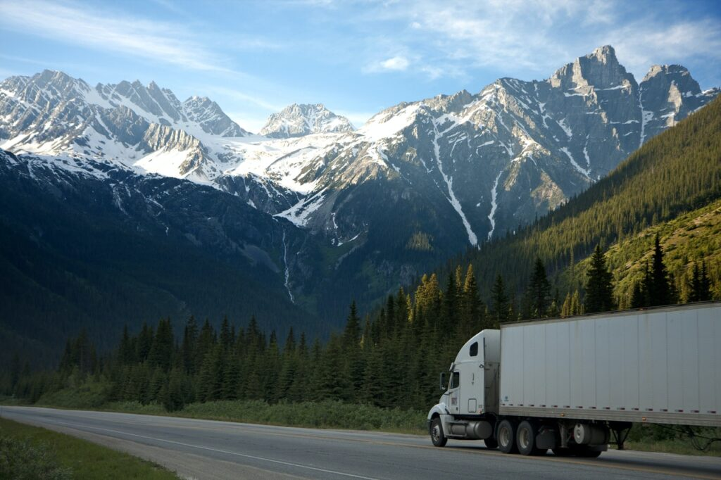 Kuorma-auto ajamassa tiellä, jonka reunoilla on havumetsää. Taustalla näkyvät suuret, lumiset vuorenhuiput.
