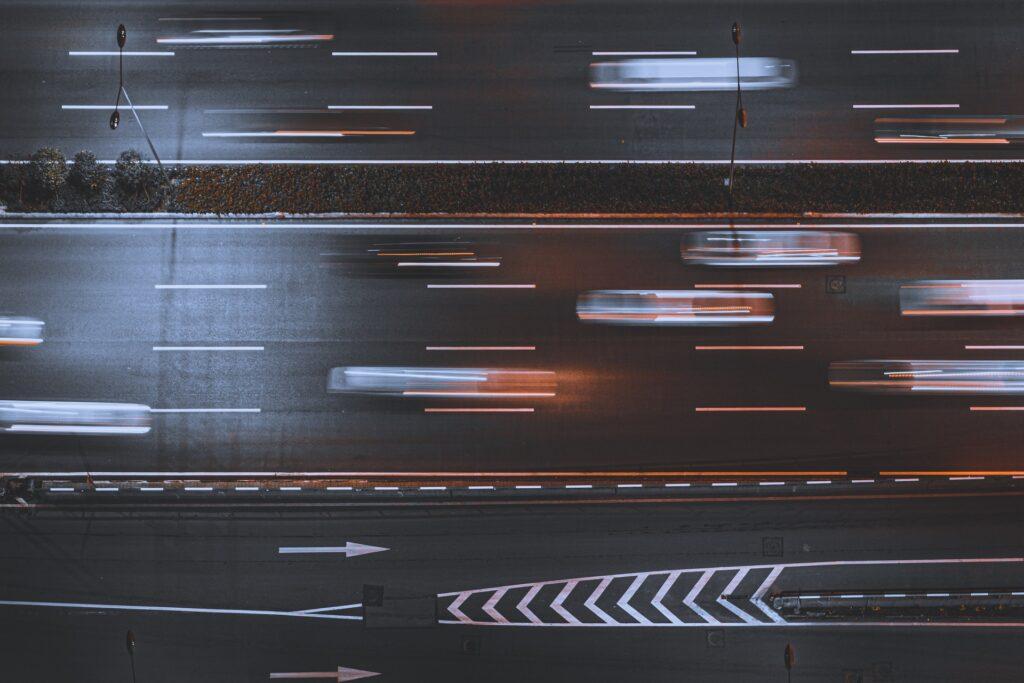 Ylhäältäpäin kuvattu moottoritie. Tiellä on monta liikkuvaa autoa, joiden ääriviivat ovat epäselvät.