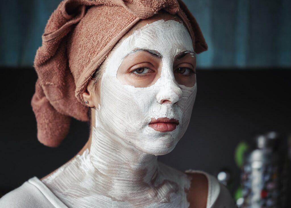 Pyyhepäinen naishahmo, jonka kasvoilla ja kaulalla on valkoista tahnaa. Silmien ympärillä ja huulilla tahnaa ei ole. Hahmolla on vakava ilme.