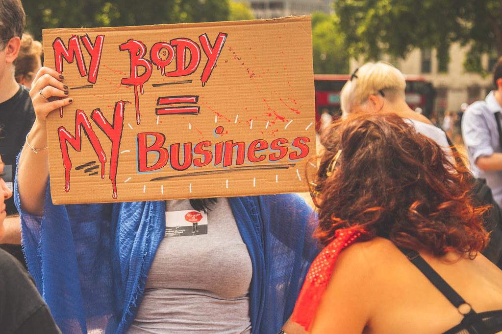 """Ihmisiä mielenosoituksessa. Henkilö peittää kasvonsa kyltillä, jossa lukee """"My body = my business""""."""
