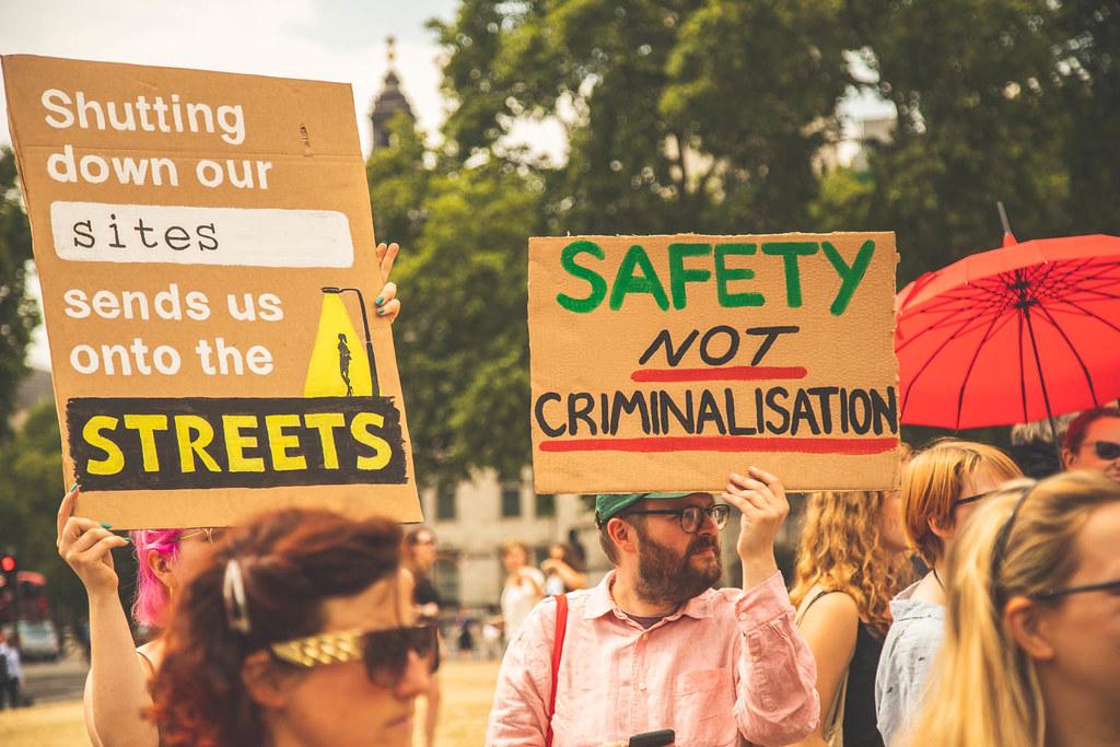 """Ihmisiä mielenosoituksessa. Yhden henkilön kyltissä lukee """"Shutting down our sites sends us onto the streets"""". Toisen kyltissä lukee """"Safety not criminalisation"""". Kolmannella on punainen sateenvarjo kädessään."""