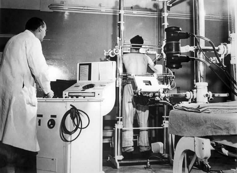 Paidaton työntekijä seisomassa röntgenkuvauslaitteessa selin kameraan. Etualalla valkotakkinen henkilö. Mustavalkoinen valokuva.
