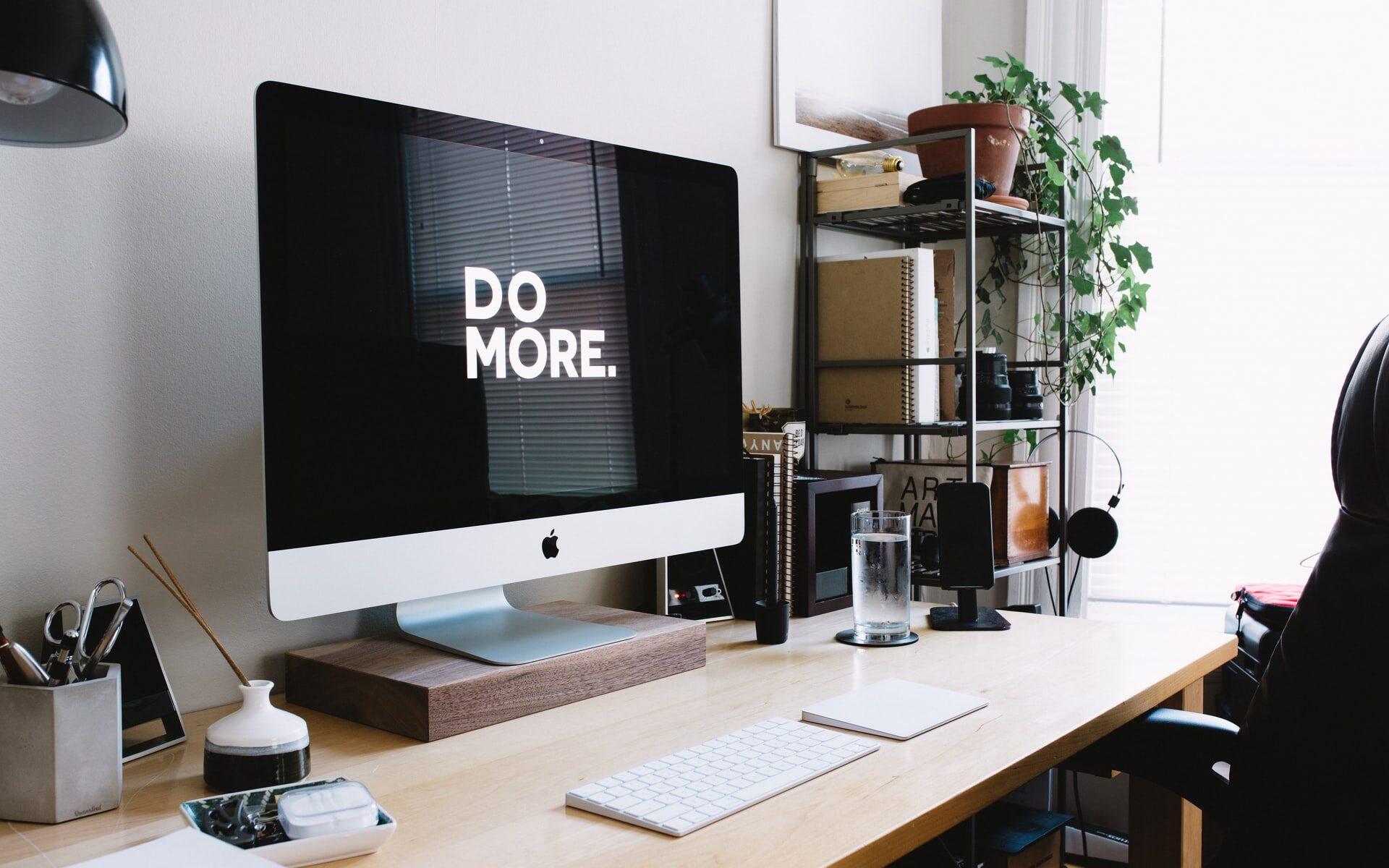 """Työpöydällä oleva Applen tietokone, jonka näytöllä lukee """"Do more""""."""
