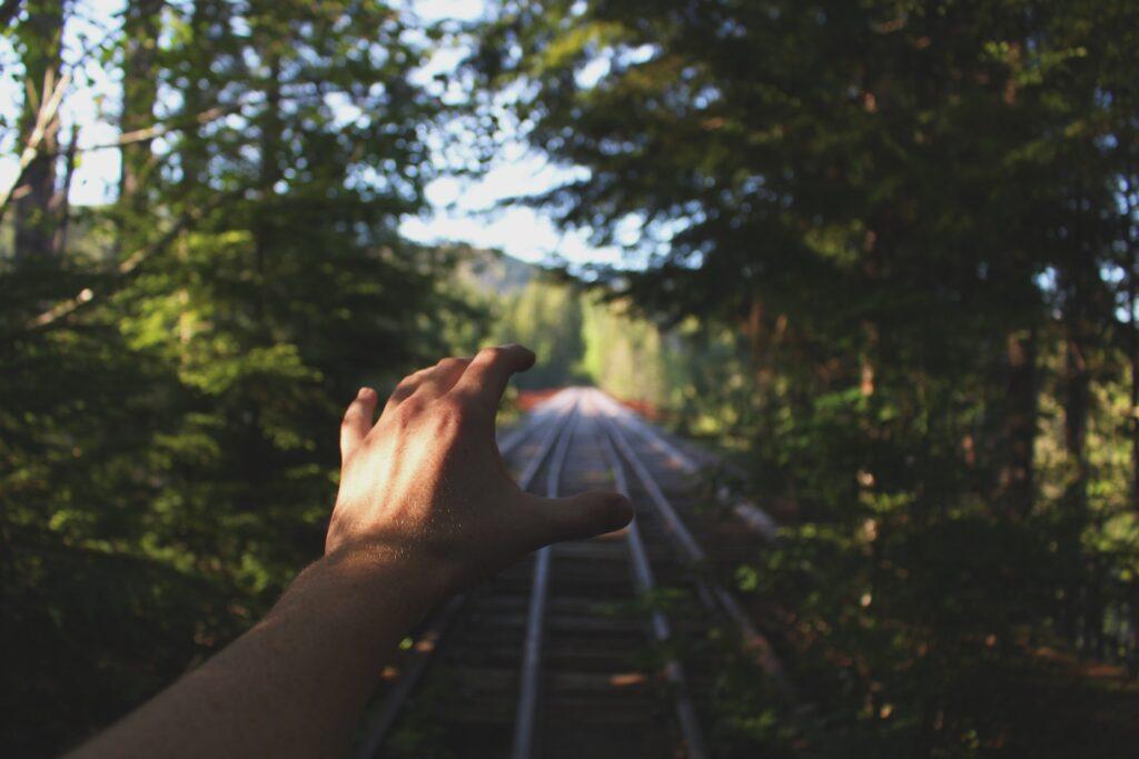 Kaukaisuuteen kurottava käsi, jonka omistaja seisoo junan raiteilla.