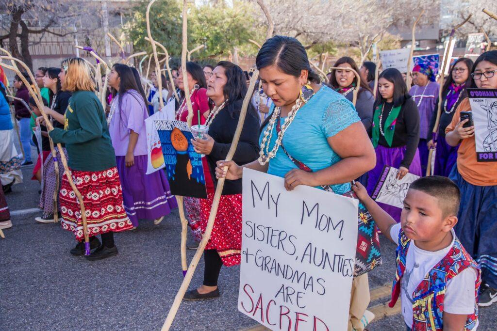 """Alkuperäiskansoihin kuuluvia ihmisiä mielenosoituksessa. Kuvan etualalla olevalla henkilöllä kyltti, jossa lukee """"My mom, sisters, aunties + grandmas are sacred""""."""