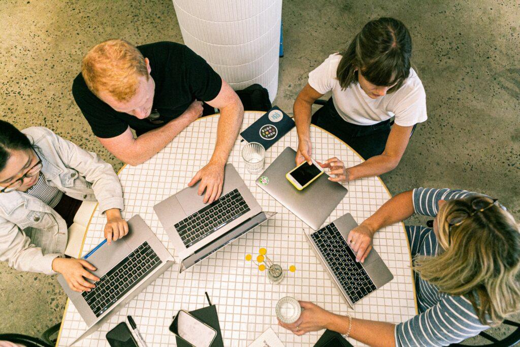 Neljä henkilöä läppäreiden kanssa saman pöydän ääressä.