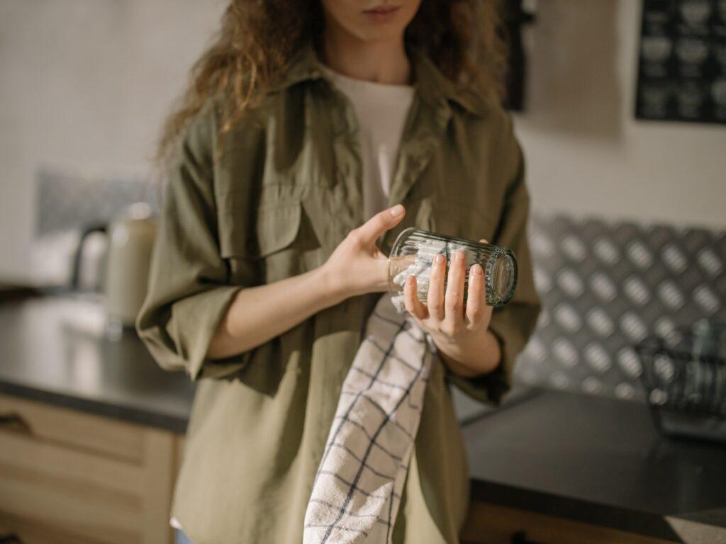 Henkilö kuivaa lasia pyyhkeellä keittiössä.