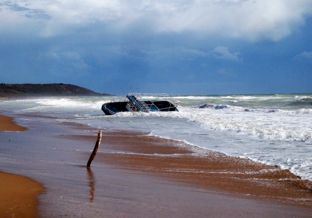 Haaksirikkoutunut vene hiekkarannan aalloissa.