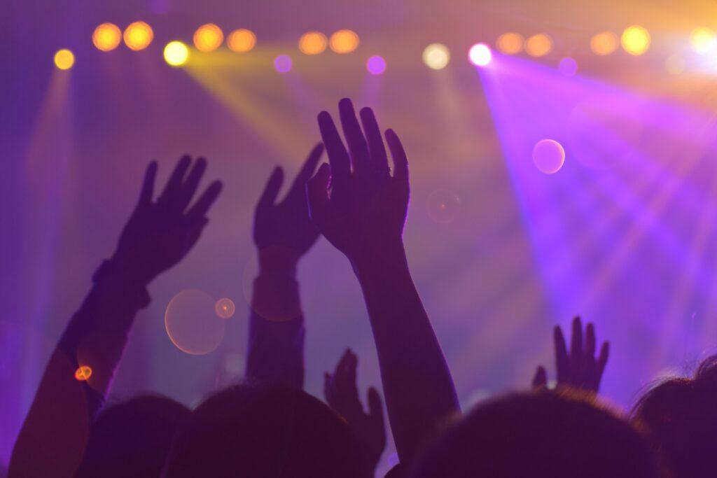 Etualalla ylös nostettuja käsiä ja taka-alalla värivaloja.