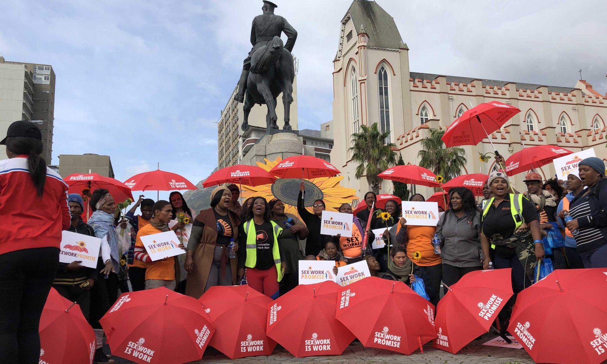 """Henkilöitä seksityötä puolustavassa mielenosoituksessa. Monella on punainen sateenvarjo, jossa lukee """"Sex work is work"""" ja """"Sex Work Promise""""."""