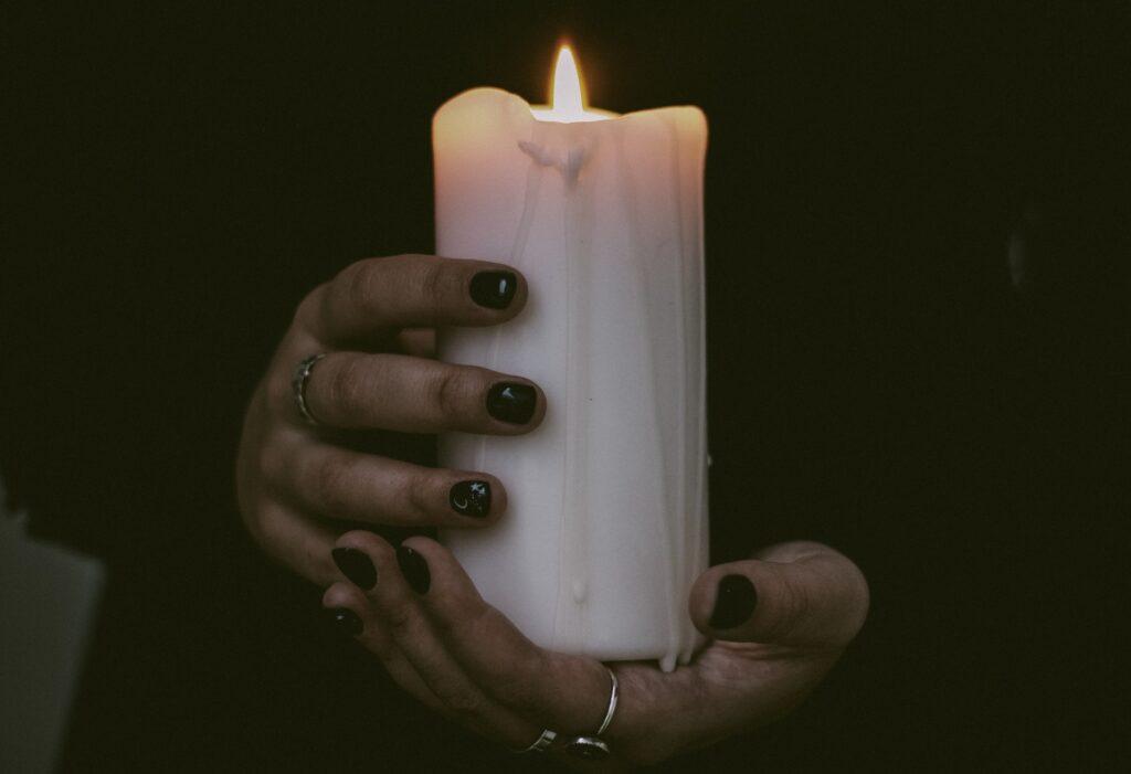 Henkilö, jolla on mustat vaatteet ja mustaa kynsilakkaa pitelemässä käsissään paksua valkoista palavaa kynttilää.
