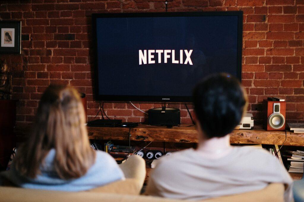 Kaksi henkilöä sohvalla katselemassa taulutelevisiosta Netflixiä.
