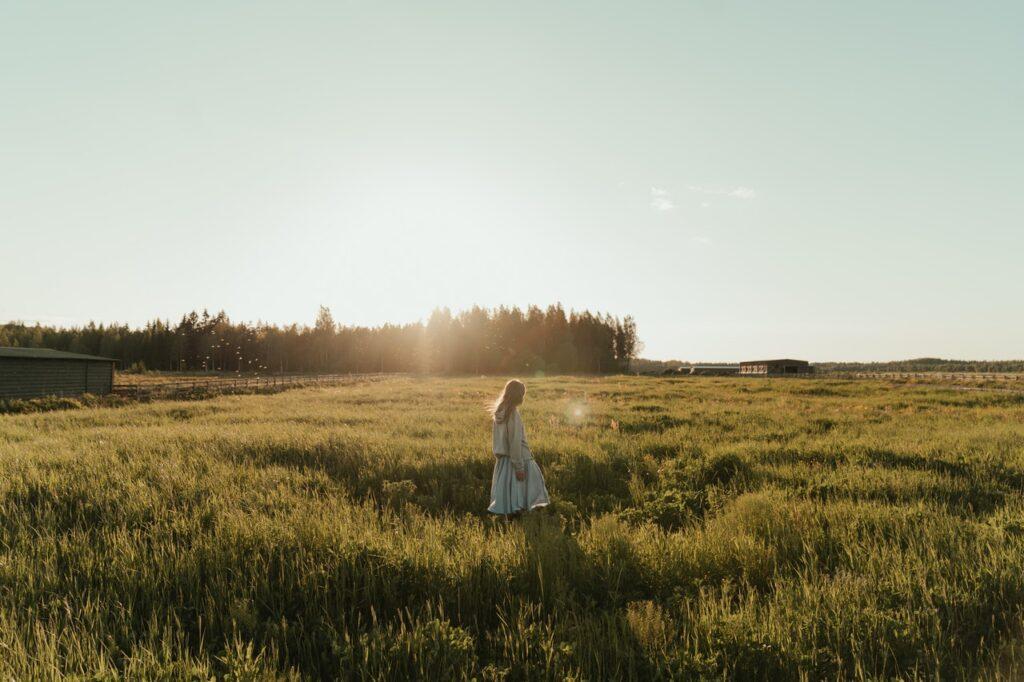 Naishahmo kävelee aurinkoisella pellolla.
