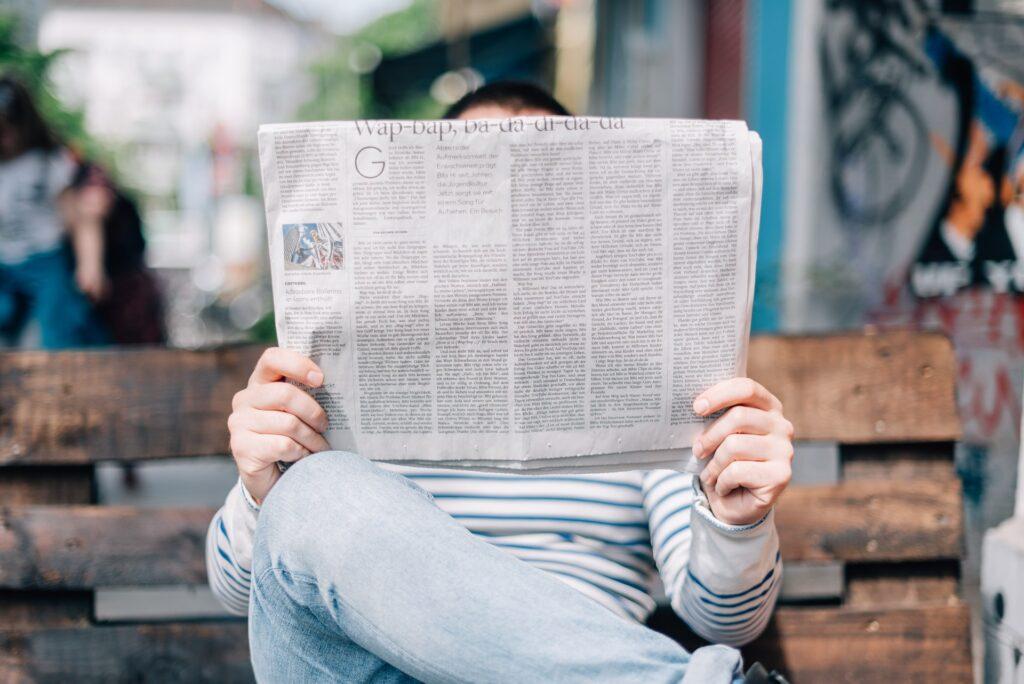 Henkilö lukemassa sanomalehteä.