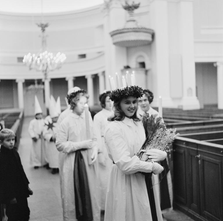 Lucian päivä. Lucia-neito Ingeborg Spiik seurueineen Tuomiokirkossa. Volker von Bonin/Helsingin Kaupunginmuseo.