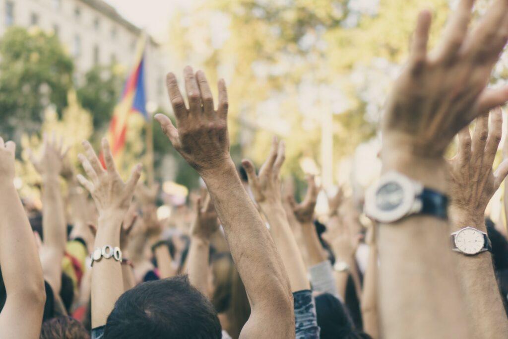 Ihmisjoukko, joka on nostanut kätensä ilmaan.