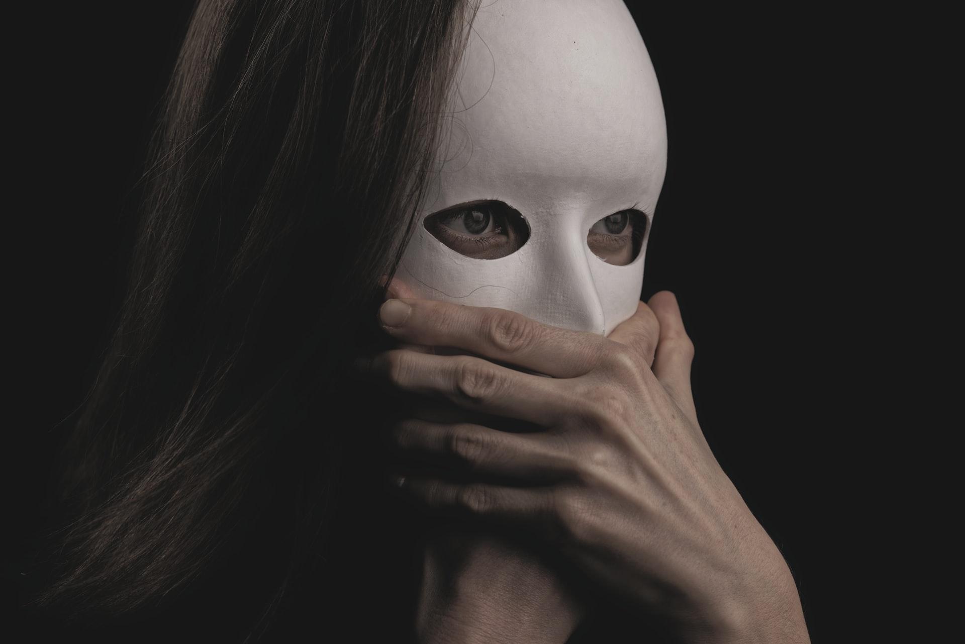 Henkilö, jolla on valkoinen kasvot peittävä naamari. Henkilön silmät näkyvät naamarin aukoista, mutta suuta peittävät kädet.