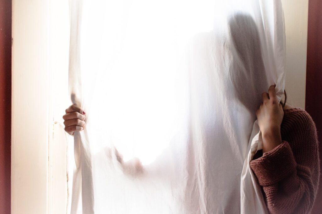 Henkilö verhon takana piilossa niin, että hänen kasvojaan ei näy.
