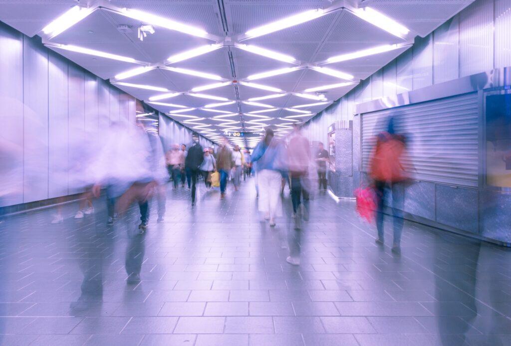 Ihmisiä liikkuu läpikulkukäytävässä. Heidän ääriviivansa eivät erotu kunnolla.
