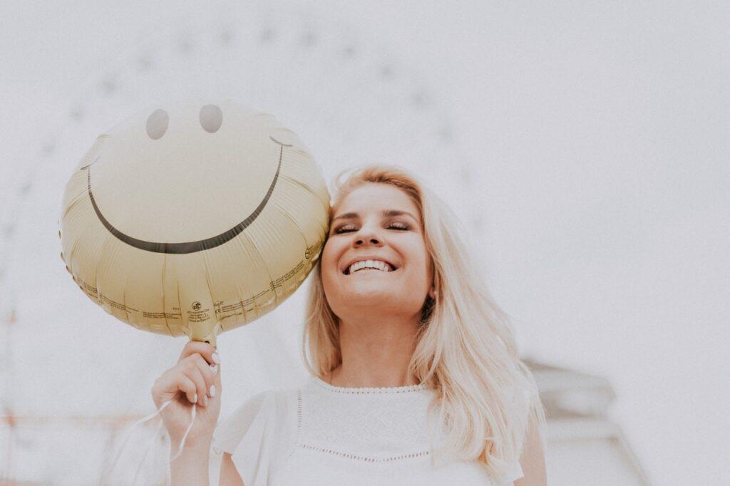 Hymyilevä henkilö, joka pitää kädessään ilmapalloa, jossa on hymynaama.