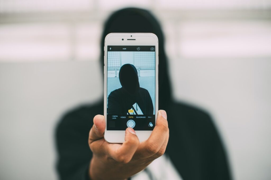 Henkilö kuvaa itseään älypuhelimella. Henkilön kasvoja ei näy kuvassa.