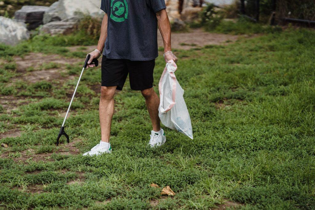 Henkilö kerää roskapihdeillä roskia pussiin nurmikolta.
