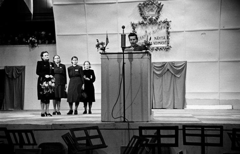 Suomen Naisten Demokraattisen Liiton (SNDL) tilaisuus Messuhallissa (Töölön kisahalli). Lavalla neljä naista ja puhuja.