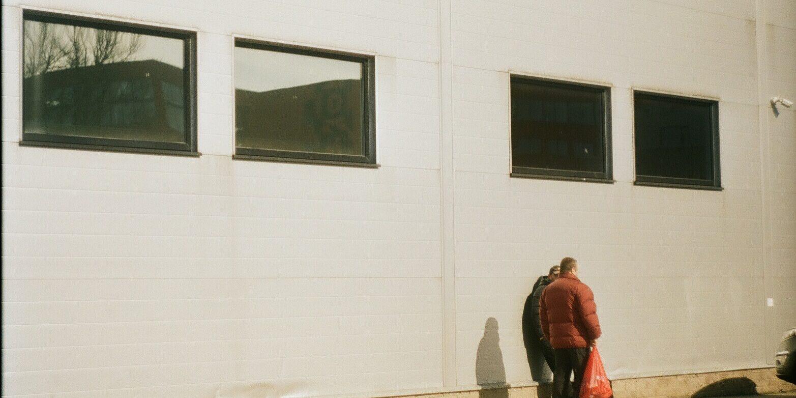 Kaksi ihmistä juttelee ison teollisuusrakennuksen edessä selin kameraan