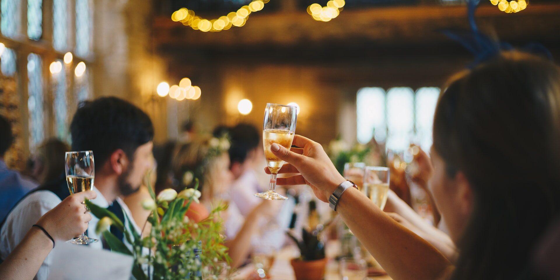 Vieraat kilistävät kuohuviinilaseja hääjuhlassa
