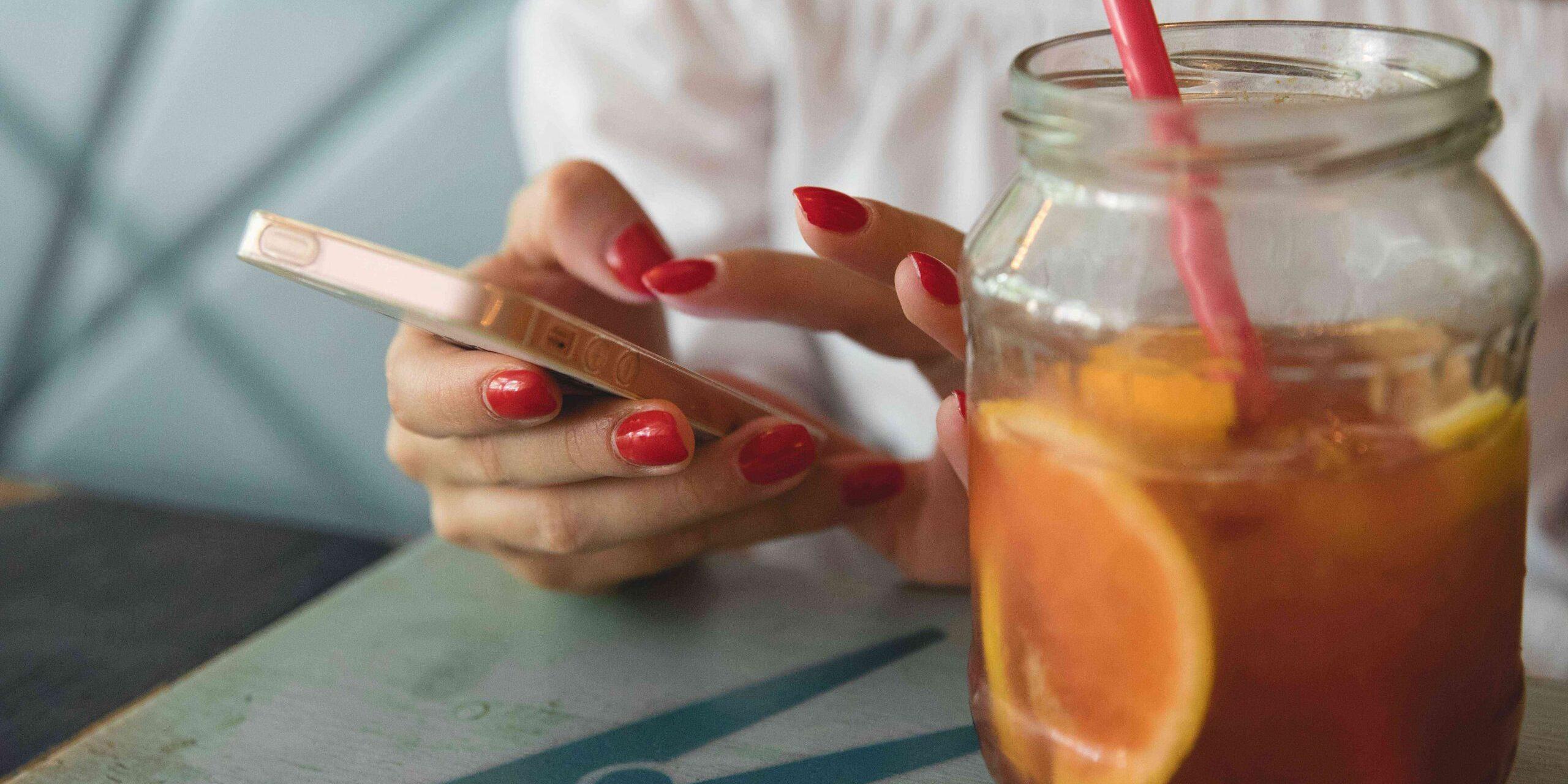 Ihminen näpyttelee älypuhelinta pöydän ääressä, pöydällä on värikäs drinkki