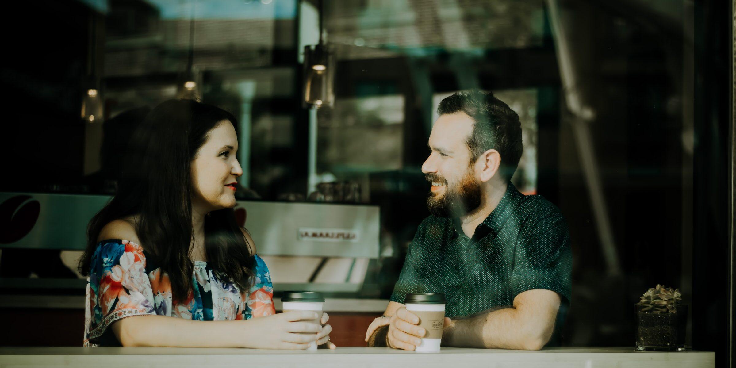 Mies ja nainen juttelevat kahvilassa