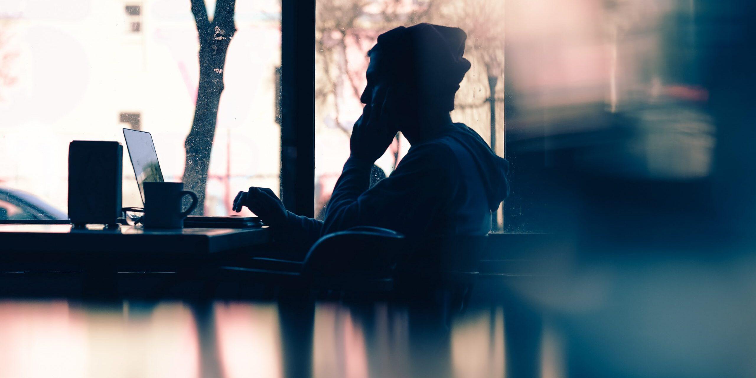 Henkilö istuu kahvilassa ikkunan vieressä läppärinsä edessä