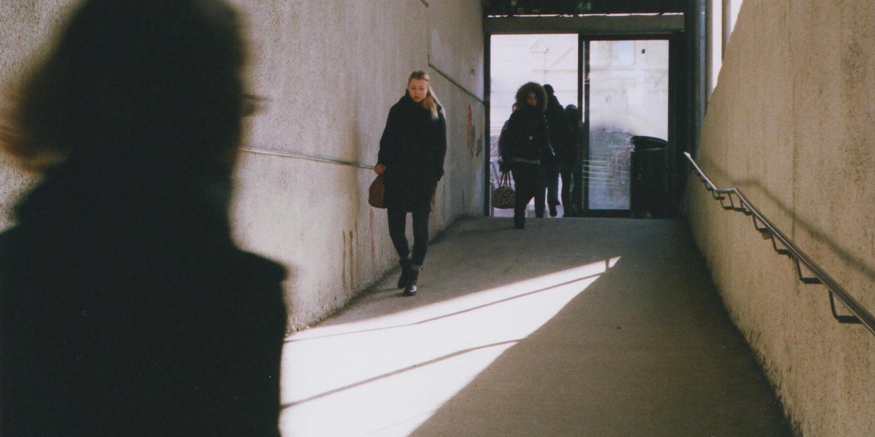 Toisiinsa etäisyyttä pitäviä ihmisiä kävelemässä käytävällä