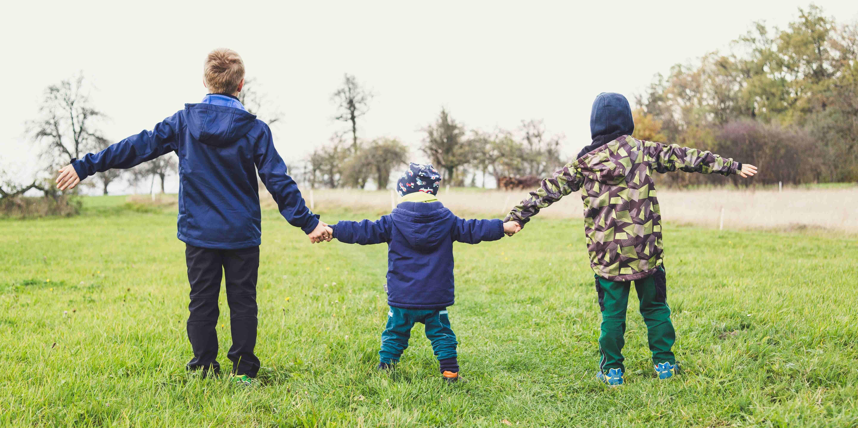 Kolme eri-ikäistä lasta pitelee toisiaan kädestä nurmikolla.