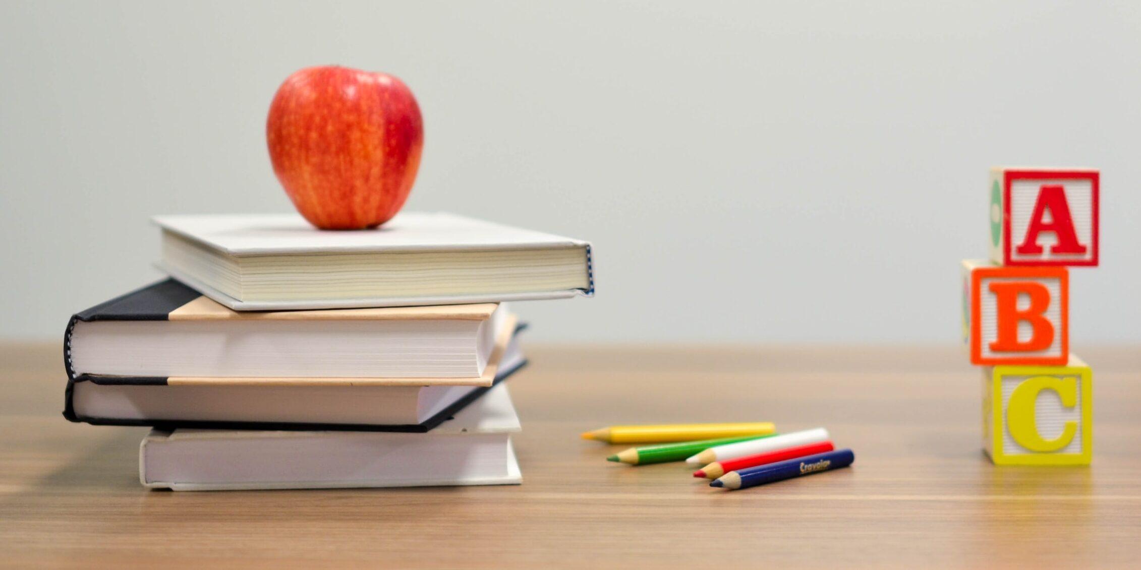 Kirjapino, kyniä, omena ja kirjainpalikoita pöydällä