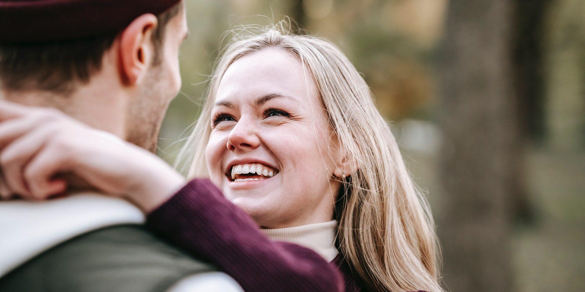 Vaalea nainen halaa miestä ja hymyilee