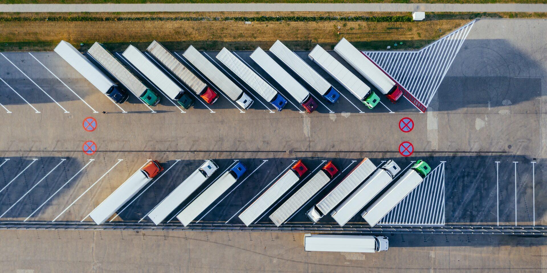 Ilmakuva parkkipaikalta, jossa on useita vinoon linjaan pysäköityjä kuorma-autoja riveissä.