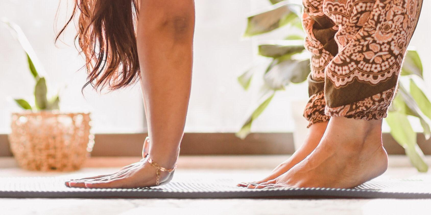 Haaremihousuihin pukeutuneen naisen kädet ja jalat joogamatolla